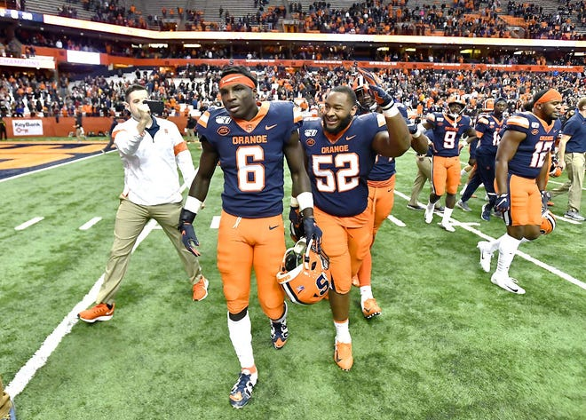 Syracuse defensive back Trill Williams (6) is congratulated by defensive lineman Curtis Harper (52) after his fumble return for a touchdown sealed a Nov. 30, 2019, win against Wake Forest in the Carrier Dome. Syracuse beat Wake Forest 39-30 in overtime.