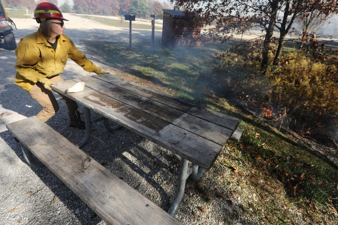 In this file photo volunteer Hillary Lee, moves a picnic table out of the way as vegetation burns during a timber burn by members of the Des Moines County Conservation and several volunteers, Thursday Nov. 5, 2020 at Big Hollow Recreation Area near Sperry. The burn was part of the conservation department's forest management efforts at the park to promote growth of the oak and hickory trees and to get rid of invasive tree species.