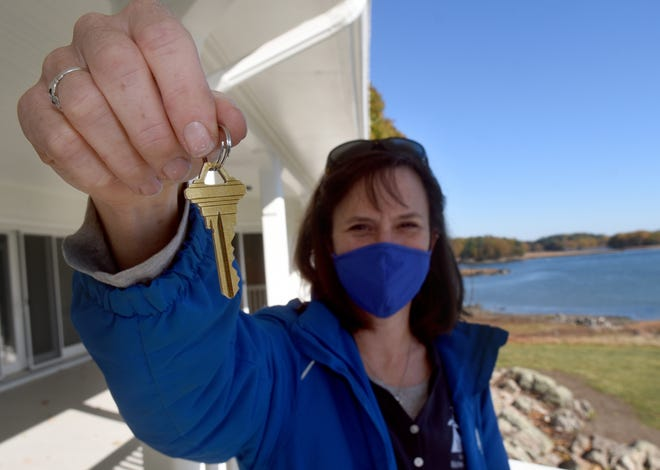 Jen Kennedy, Executive Director, Blue Ocean Society for Marine Conservation holds the key as the first tenant at Carey Cottage operated by the nonprofit group GoodWork.