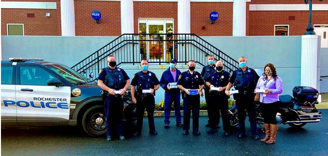 Rotarians Kerry Norton and Steve Dore deliver masks to Rochester Police Department.