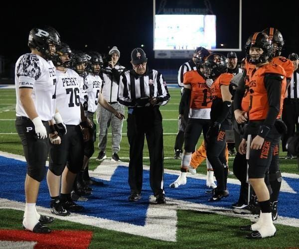 Captains for Perry and Massillon meet at midfield prior to last year's Division II regional semifinal game at Lake