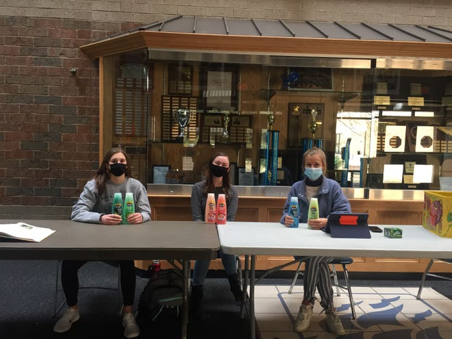 From left, Hudson High School students Peyton Binns, Megan Earp, and Claire Campanelli help to collect donations in the morning as National Honor Society members.