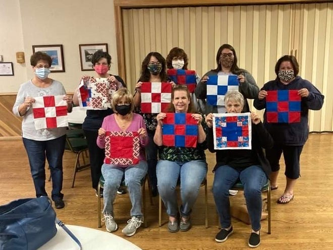 Members of American Legion Auxiliary Unit 281 showing off some of the quilt blocks they stitched together.