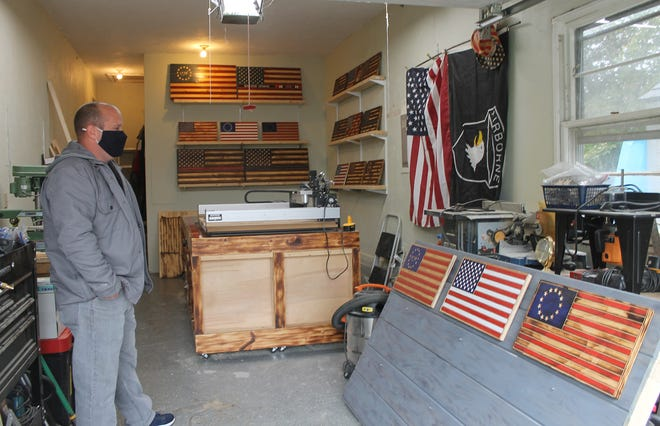 Tim Berry, founder of 1776 Flag Company, makes the custom wooden flags in his the garage of his Portsmouth home.