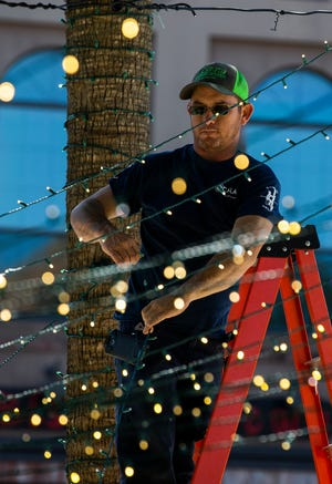 "City of Ocala Electric Utility truck operator Weston Downs helps put up holiday lights on the downtown square last week. OEU has won a ""Building Strong Communities"" award from the Florida Municipal Electric Association (FMEA)."