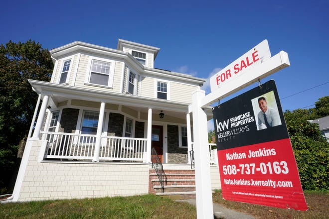 A for sale sign stands in front of a house, Tuesday, Oct. 6, 2020, in Westwood, Mass.  Even with mortgage rates hovering near all-time lows, rising home prices are putting more pressure on buyers to come up with a bigger down payment.