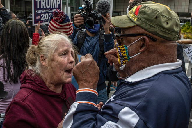 A supporter of President Trump, left, argues with another protester during a stop the vote rally last month outside the TCF Center in Detroit, where ballots were being counted.