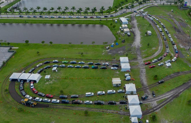 WEST PALM BEACH -- People wait in their cars to be tested for the coronavirus with drive-up rapid testing at the FITTEAM Ballpark of the Palm Beaches recently. [GREG LOVETT / THE PALM BEACH POST]