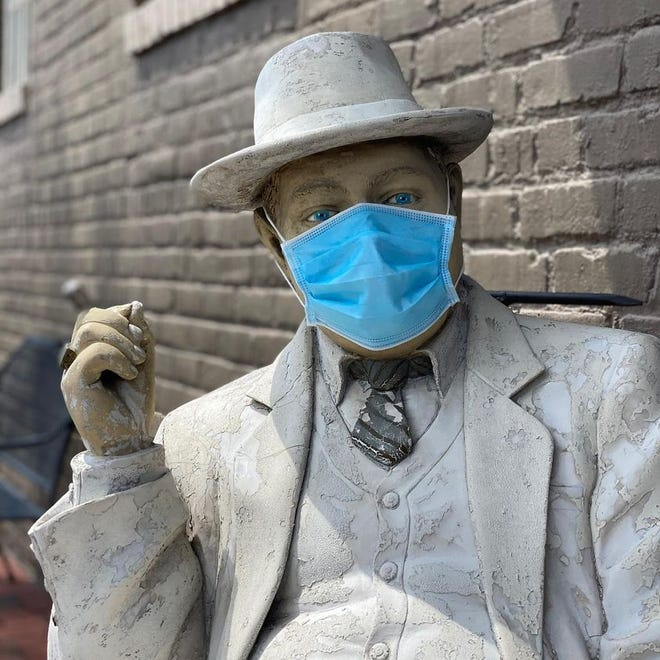 'Truman Capote' statue wearing a face mask sits near the entrance of Demolition Coffee in Old Towne Petersburg.