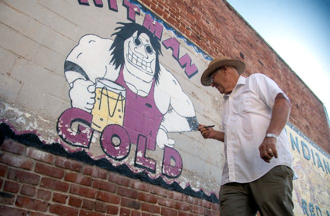 Dennis Cochran works to restore one of three murals on the back wall of Valley Brew on Adams Street and Pacific Avenue on the Miracle Mile in Stockton.