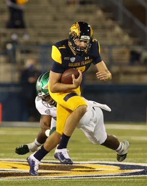 Kent State senior quarterback Dustin Crum scrambles with the ball during Wednesday night's game against Eastern Michigan.