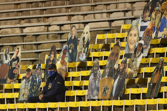 Kent State University President Todd Diacon, surrounded by cardboard cutouts, is the sole spectator at last Wednesday night's season opener against Eastern Michigan at Dix Stadium.