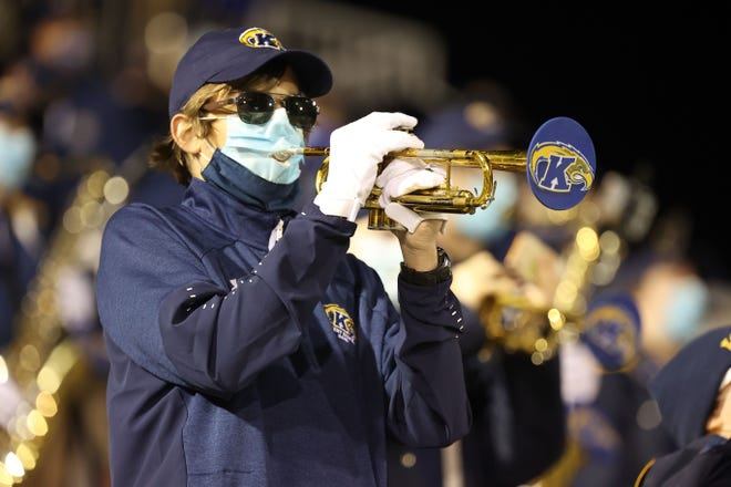 A trumpet player in the Kent State University Marching Band uses a modified face mask and cloth trumpet bell cover to mitigate the spread of COVID-19 during last Wednesday's game against Eastern Michigan at Dix Stadium.