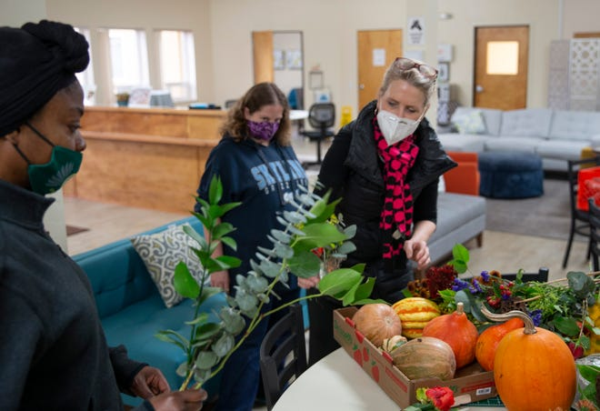 Beth Sheehan, right, leads a flower arranging class at the Eugene Mission, for participants in the Rescue, Revitalize and Restore program.