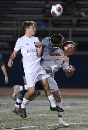 Ethan Corsi (left) and Troy Atkinson (5) of Jackson goes for a header with Nasser Tahat (center) of Hudson during their Division I regional semi final game at Hudson on Wednesday, Nov. 4, 2020.