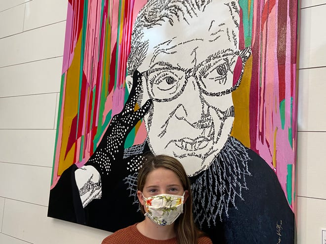 "South Rock Creek sixth grader and 12-year-old essay finalist Isabelle O'Daniel admiring a piece from Shawnee artist LeAnne Henry Wright's ""I Dissent."" art show."