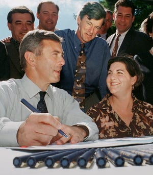 Then-Massachusetts Gov. Paul Cellucci, left, and former Lt. Gov. Jane Swift, right, share a light moment as former Mass. Environmental Affairs Secretary Bob Durand, center, looks on during the Community Preservation Act signing ceremony in 2000 in Waltham.