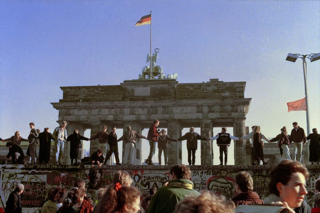 This Nov. 10, 1989, file photo shows Berliners singing and dancing on top of the Berlin wall to celebrate the opening of East-West German borders. Thousands of East German citizens moved into the West after East German authorities opened all border crossing points to the West. In the background is the Brandenburg Gate. Monday, Nov. 9, 2020, marks the 31st anniversary of the fall of the Berlin Wall.