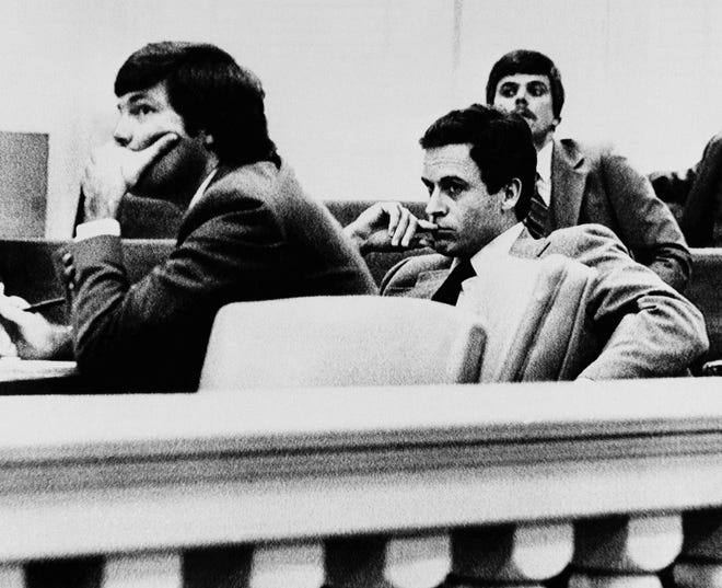 Theodore Bundy, right, listens intently with public defender Lynn Thompson, left, during examination of prospective jurors, Nov. 6, in Live Oak, Fla. Bundy is accused of murdering 12-year-old Kimberly Leach who was abducted from her school in Lake City, Fla. in February of 1978.