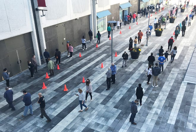The line for free COVID-19 tests snakes across the Mercantile Center courtyard Thursday in downtown Worcester