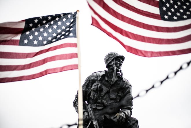 Flags blow in the wind by the Iron Mike statue at the Airborne & Special Operations Museum on Monday, May 18, 2020.