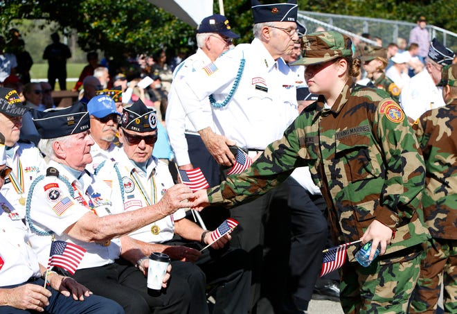Members of the Milton Lewis Young Marines, right, hand out small American flags during the 2019 Veterans Day Celebration at Kanapaha Veterans Memorial Park. Due to the COVID-19 pandemic, the city of Gainesville and Alachua County will be turning to virtual events to honor America's military veterans.