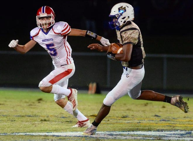 Eastern Guilford quarterback Kamell Smith, right, is chased by Southern Alamance's Emmett Raggett.