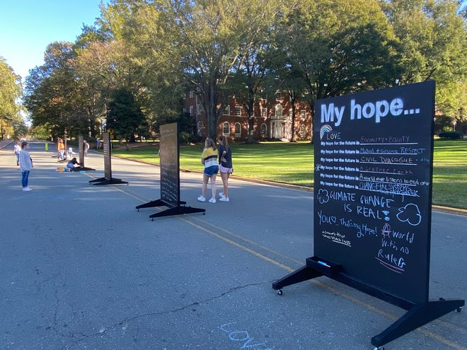 Students wander around Wednesday, Nov. 4, reading the messages added to double-sided chalkboards set up on Haggard Avenue in Elon as part of Hopes for the Future: Public Art Project. [ELIZABETH PATTMAN / TIMES-NEWS]