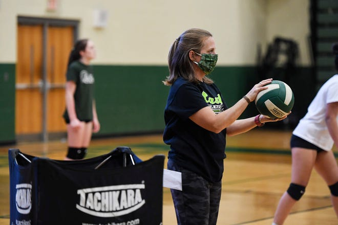 East Henderson JV coach Elizabeth Pippin serves volleyballs to her team during practice November 4, 2020.