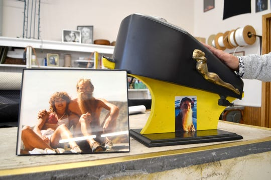 """A custom motorcycle gas tank made by Gerald """"Jerry"""" Schleis, featuring a bronze-cast copy of a hood ornament he made and added to it, is shown alongside a late-1980s photo of Schleis and his wife, Marie Farrell."""