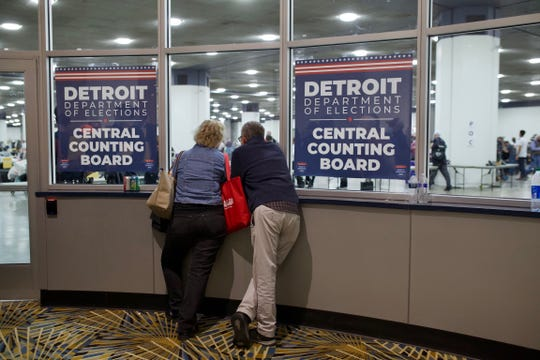 Two people look through the glass as they wait to be called to go in as poll observers at the TCF Center in Detroit, Wednesday, Nov. 4, 2020.