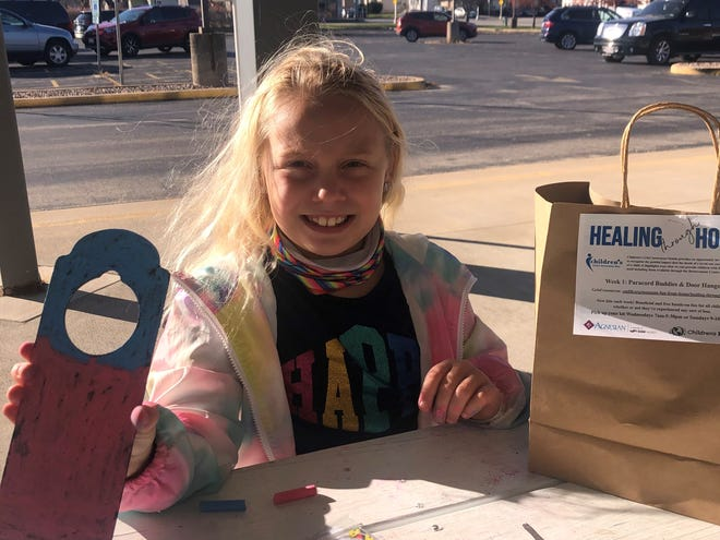 Mia Graham shows off her completed door hanger from the first Healing Through Hope November activity kit for Children's Grief Awareness Month at the Children's Museum of Fond du Lac.