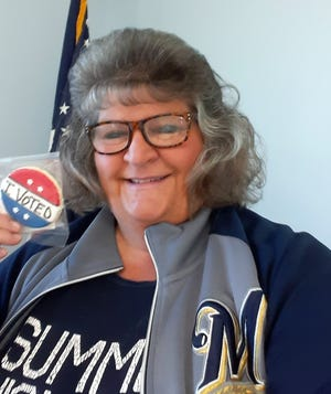 """Cheryl Field, the Doty Town Clerk, holds a sugar cookie decorated to look like an """"I Voted"""" sticker, which were handed out to voters after they cast their ballots on Tuesday."""