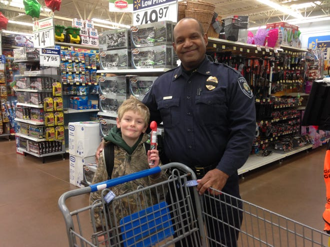 Sgt. Bill Darnell of the DeWitt Township Police helped Owen Gibson, a six-year-old from Oakview Elementary in St. Johns, do some shopping during the annual Shop with a Cop event at Walmart in St. Johns Dec. 11, 2014.