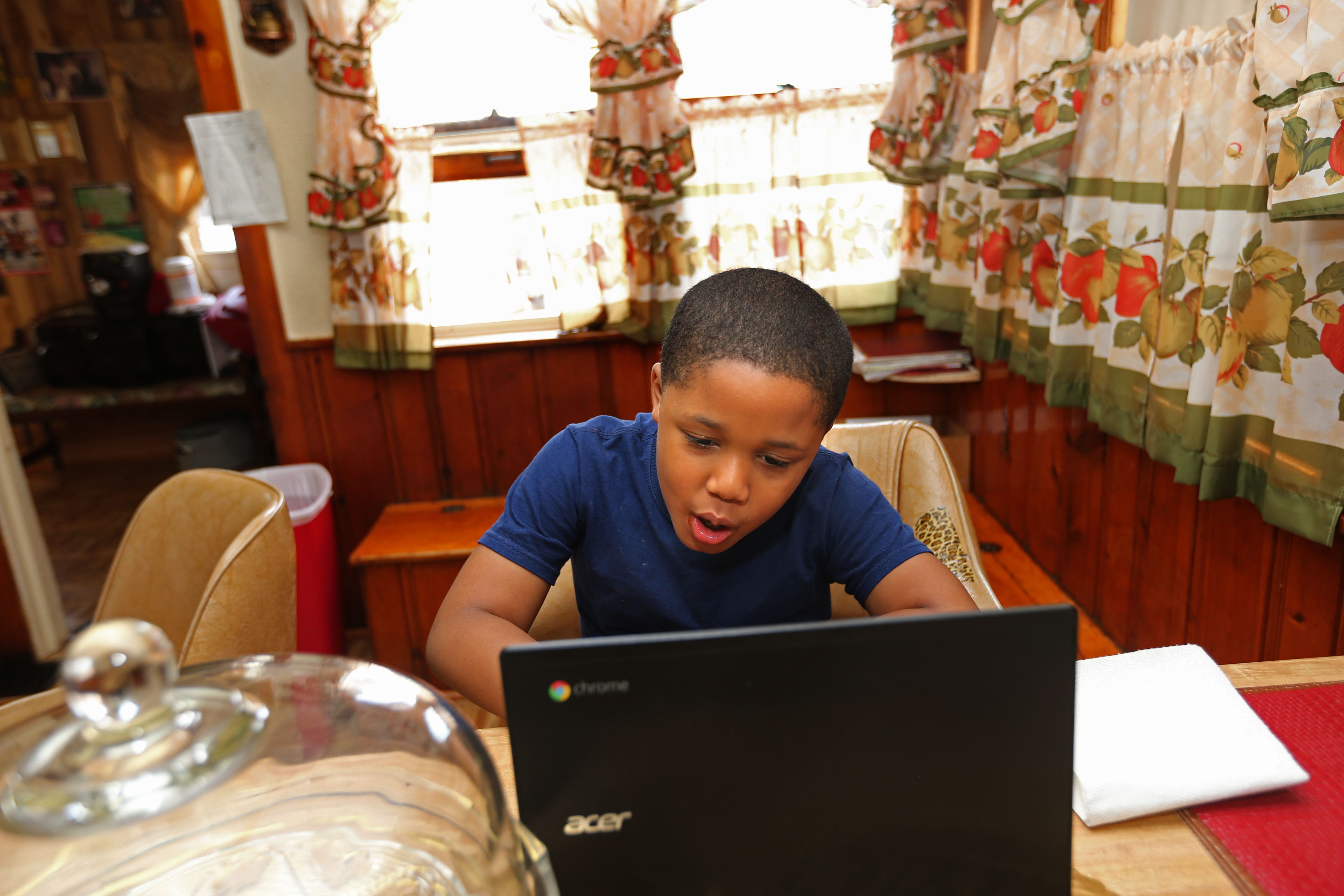 Josiah Johnson, 7, a second grader at Ralph H. Metcalfe School,  receives help from his MKE Fellows mentor and tutor Malachi Crenshaw at his grandmother's home. The program has been mentoring and helping students like Johnson with their classwork during the coronavirus pandemic.