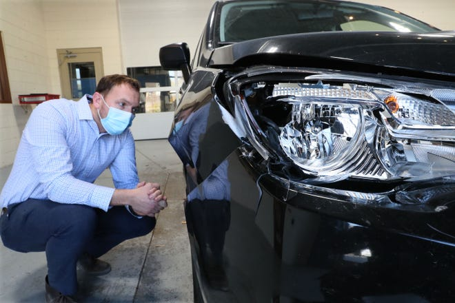 Jim Keller owner, of 1 Collision in Menomonee Falls looks over damage to the front end of a 2017 Subaru Forester caused by a collision with a deer.  The vehicle was brought in for repair.  Damage includes busted out headlight and trim and protective housing over it, hood pushed back, bumper damage, then further down the side of the car doors dented as the deer tumbled past.