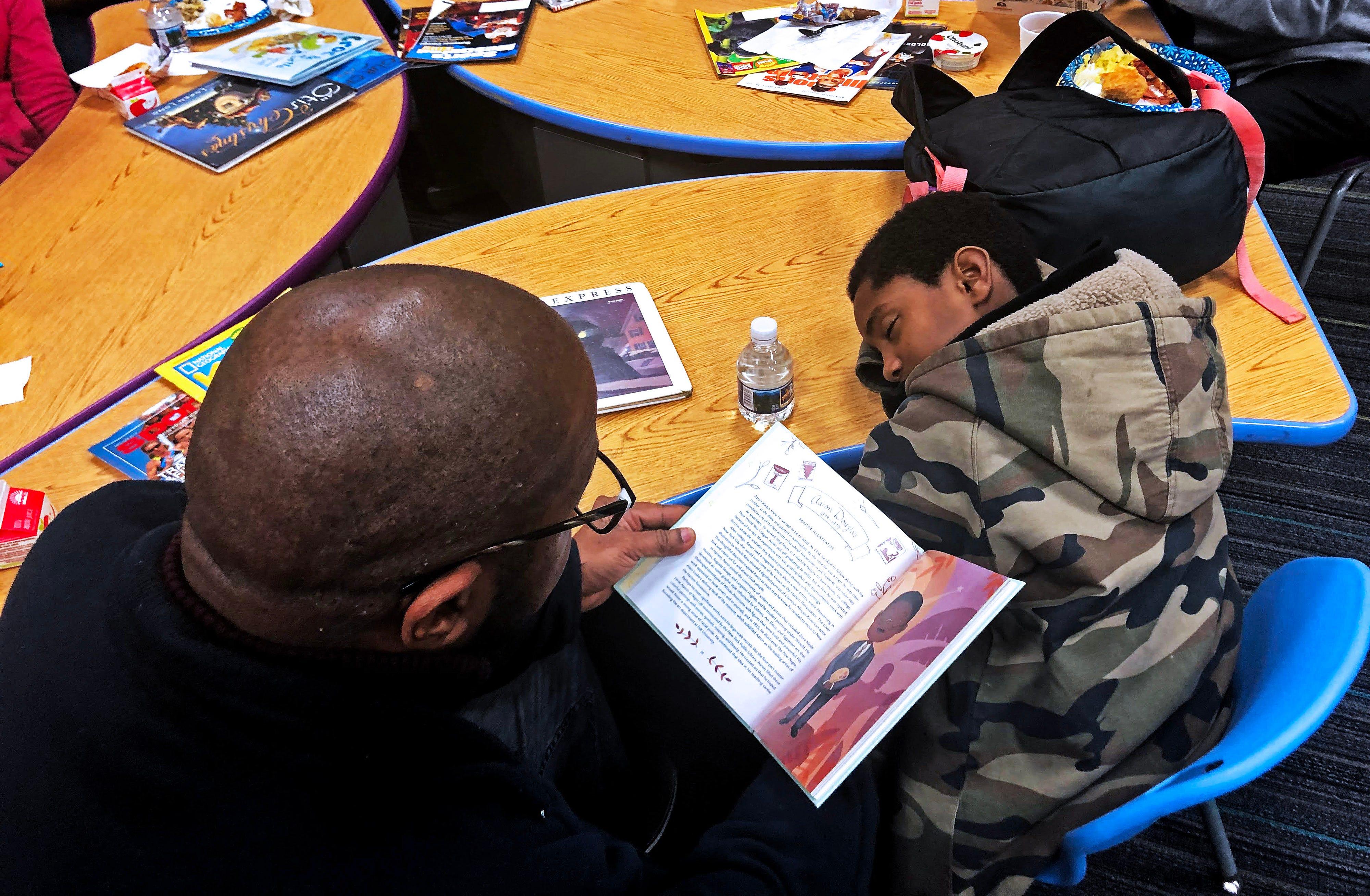 Carlton Atkins, 47, reads to David Nathan at Buena Vista Elementary School in Nashville, Tennessee.
