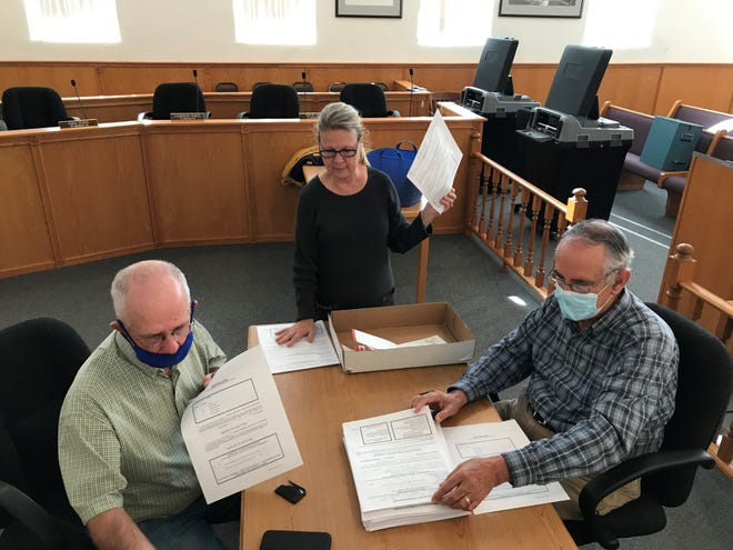 Members of the Baxter County Election Commission, from left, Bob Bodenhamer, Judy Garner and Rick Peglar review a stack of provisional ballots Wednesday morning at the Baxter County Courthouse.