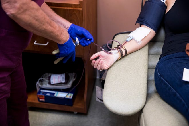 """Angie Mikat donates plasma at the Lee Health Blood Center at Summerlin Crossing on Thursday, November 5, 2020. She is a recovered Covid-19 patient who was donating convalescent plasma to help current patients with the disease. She said """"It is a way to give back and help."""""""