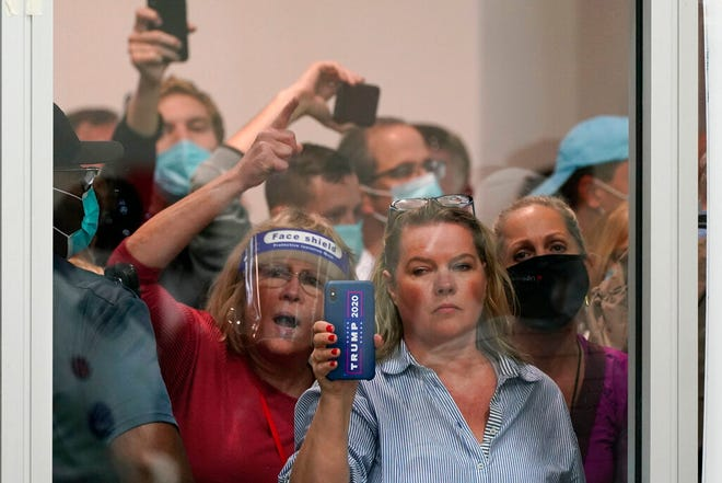 People wanting to be election challengers yell as they look through the windows of the central counting board as police were helping to keep additional challengers from entering due to overcrowding, Wednesday, Nov. 4, 2020, in Detroit. (AP Photo/Carlos Osorio)