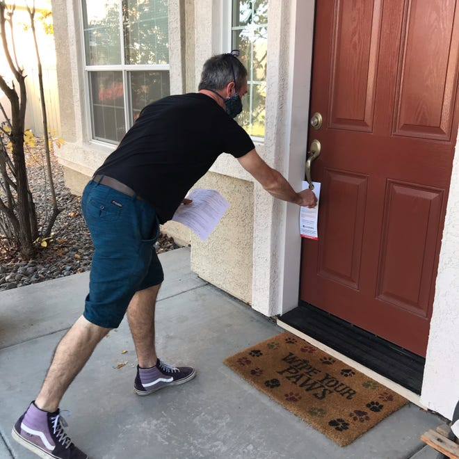 Riley Sutton places a ballot rejection notification on a doorknob in south Reno.