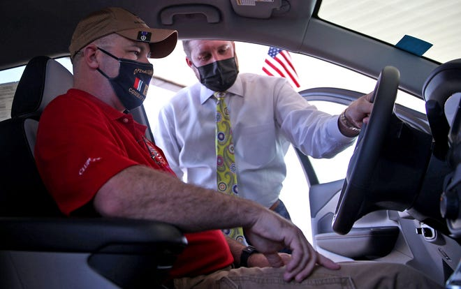Retired U.S. Air Force Staff Sgt. George Campbell, left, is told about the features of his new vehicle by Mitchell Buick-GMC Sales Representative Greg Herridge, center, at an event in front of the dealership Thursday, Nov. 5, 2020.
