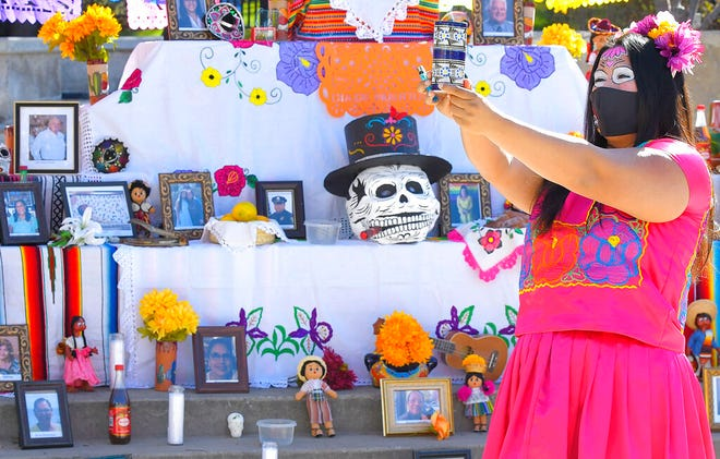 Lizette Villegas performs a blessing on an Ofrenda for those who died of COVID-19, as part of Día de Muertos celebration on Monday, Nov. 2, 2020, in Logan, Utah. (Eli Lucero//The Herald Journal via AP)