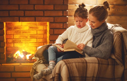 A mother and daughter read a book near a fireplace