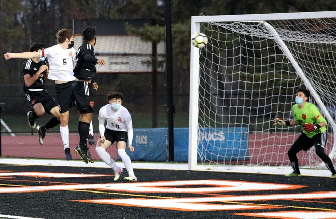 Mamaroneck's James Jogis heads the ball toward the net for a goal, over White Plains' Luis Fernando Zapata, during the Mamaroneck vs. White Plains boys soccer game at White Plains High School, Nov. 4, 2020. They tied at 1-1 in double overtime.