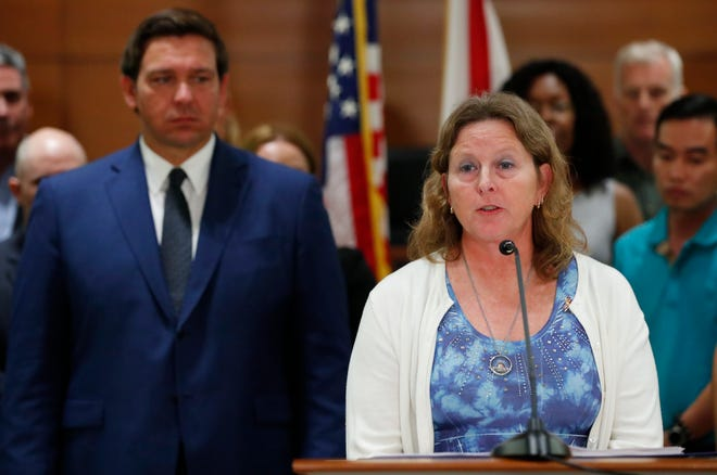 In this Wednesday, Feb. 13, 2019 photo, Debra Hixon, wife of Marjory Stoneman Douglas High School athletic director Chris Hixon, who was killed during a school shooting, speaks as Florida governor Ron DeSantis, left, looks on during a news conference, in Fort Lauderdale, Fla. Hixon, easily won election to the nine-member Broward County school board.