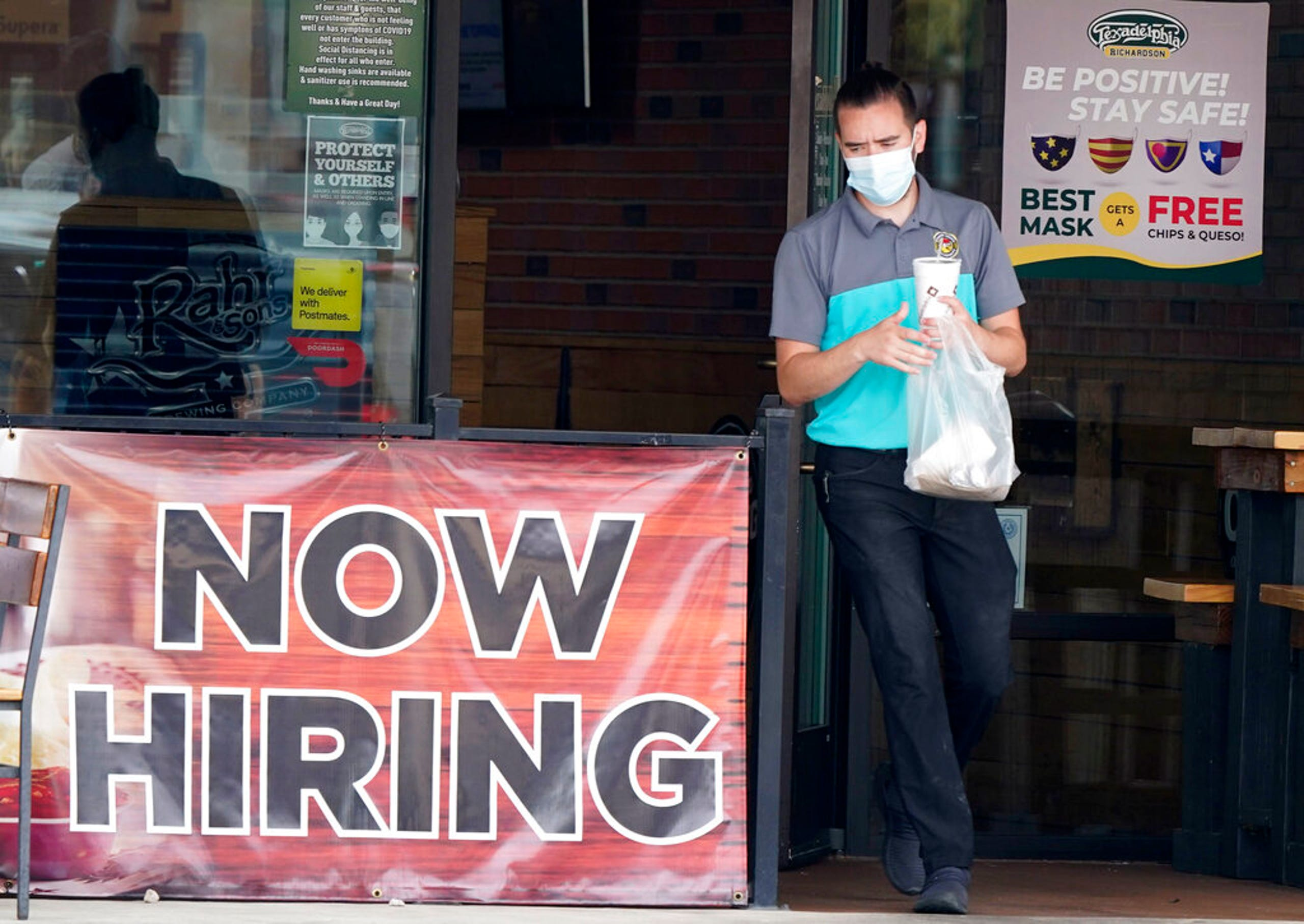 In this Sept. 2, 2020 file photo, a customer wears a face mask as they carry their order past a now hiring sign at an eatery in Richardson, Texas.