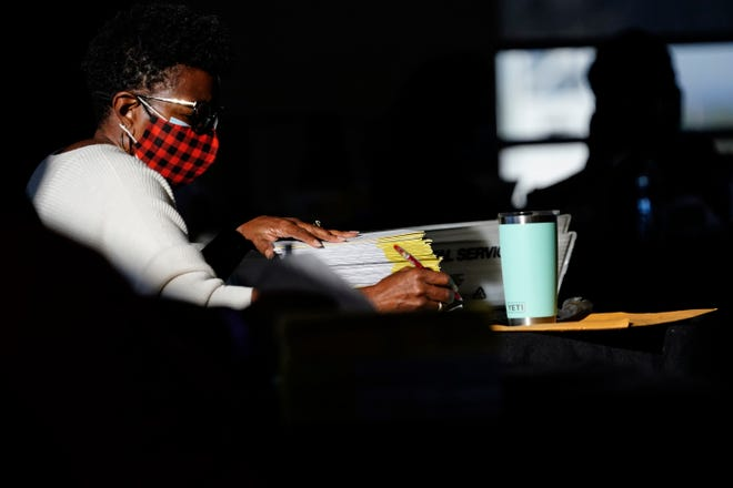 Election workers count ballots at State Farm Arena on Thursday, Nov. 5, 2020, in Atlanta.