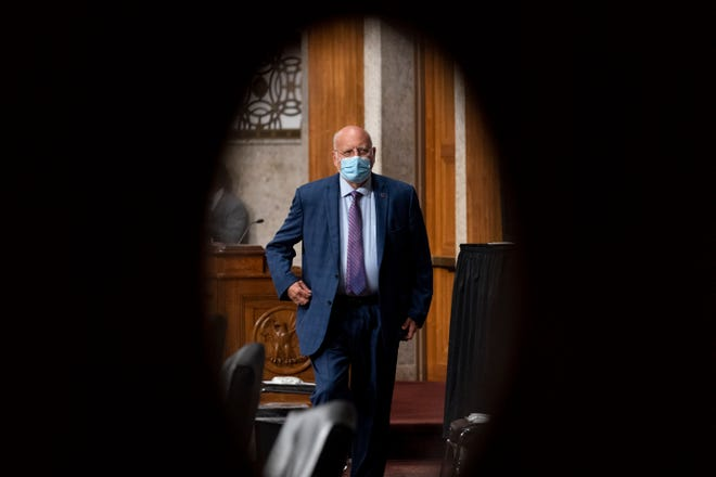 "In this Sept. 16, 2020 file photo, Centers for Disease Control and Prevention Director Dr. Robert Redfield is seen through a door window as he appears at a Senate Appropriations subcommittee hearing on a ""Review of Coronavirus Response Efforts"" on Capitol Hill in Washington."