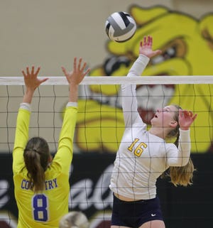 Tallmadge's Ella Bee, facing, spikes the ball over Coventry's Mallory Meinen during the first set of a Division II regional semifinal volleyball match, Thursday, Nov. 5, 2020, in Stow, Ohio. [Jeff Lange/Beacon Journal]
